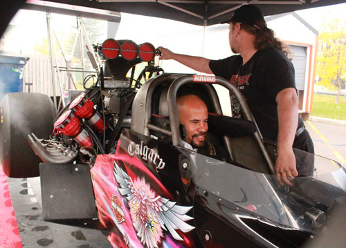 Calgary Stampeders running back Jon Cornish in cockpit of Darkside Racing Top Fuel dragster.